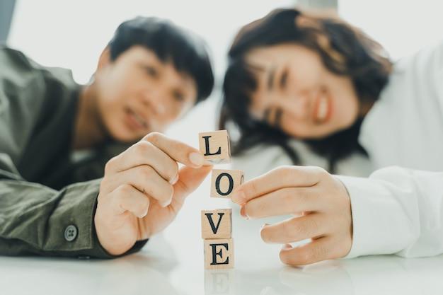 Pareja joven apilando las letras de amor juntas