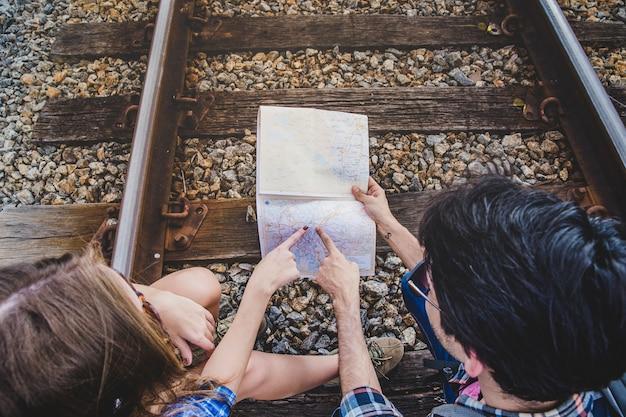 Pareja joven apuntando a mapa en vías de tren