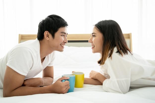 Pareja joven asiática disfrutando junto con café en la mañana en el dormitorio