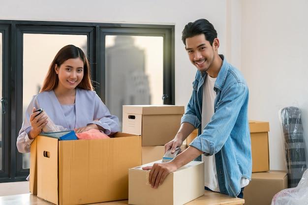 Pareja joven asiática embalaje caja de cartón grande para moverse en nuevo hogar