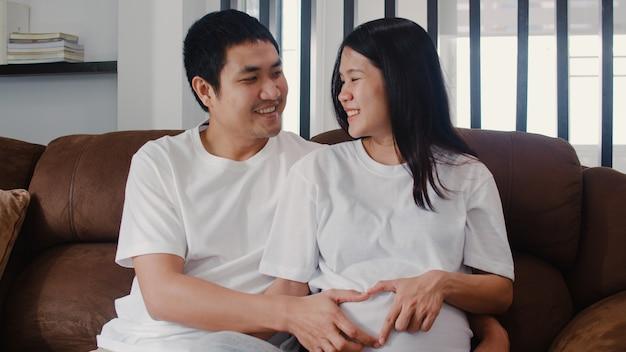 Pareja joven asiática embarazada haciendo muestra del corazón sosteniendo el vientre. mamá y papá se sienten felices sonriendo pacíficos mientras cuidan bebé, embarazo acostado en el sofá en la sala de estar en casa.