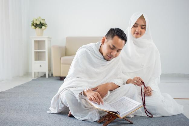 Pareja joven asiática rezando con al-qur'an y rosarios
