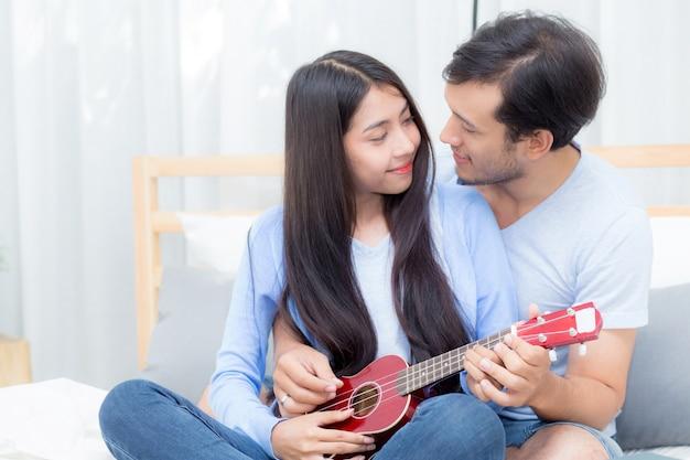 Pareja joven asiática tocando el ukelele
