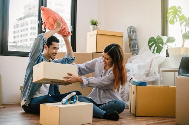Pareja joven asiático con caja de cartón grande para mudarse en casa nueva