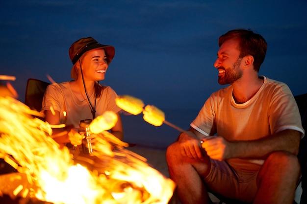 Pareja joven y atractiva se sienta en sillas plegables cerca de la carpa y asa maíz en el fuego y se divierte hablando por la noche cerca del mar.