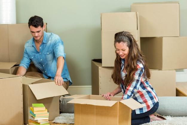 Pareja joven ayudándose mutuamente mientras desempacando cajas de cartón en casa nueva