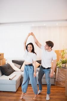 La pareja joven baila en la sala de estar cerca de cajas de cartón para entretenerse en el día de la mudanza, el esposo y la esposa felices se divierten y se trasladan a su propio apartamento juntos.