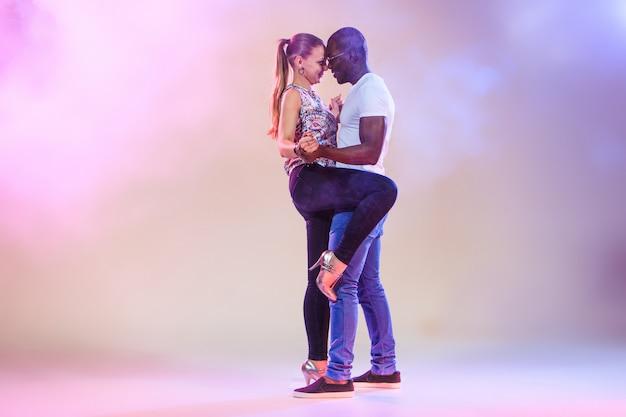 Pareja joven baila salsa caribeña social, foto de estudio