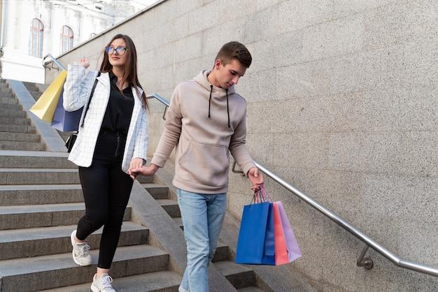 Pareja joven bajando escaleras con numerosos paquetes después de ir de compras.