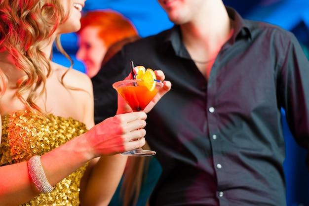 Pareja joven en bar o club bebiendo cócteles