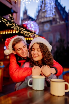Pareja joven con bebidas en el mercado de navidad en wroclaw, polonia