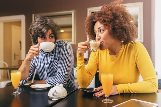 Pareja joven bebiendo café y un zumo de naranja, mirándose unos a otros