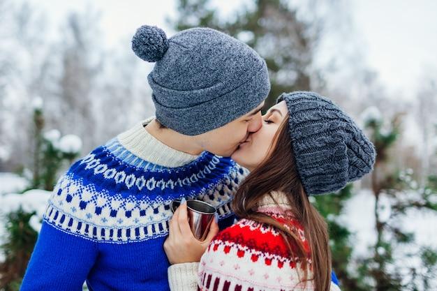 Pareja joven bebiendo té y besándose en el bosque de invierno. gente feliz descansando al aire libre durante las vacaciones
