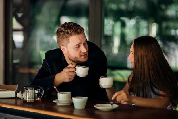 Pareja joven bebiendo té en café