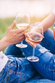 Pareja joven bebiendo vino en manos grandes de la naturaleza