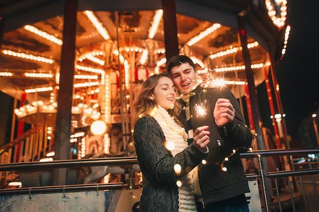 Pareja joven besándose y abrazándose al aire libre en la calle de noche en navidad