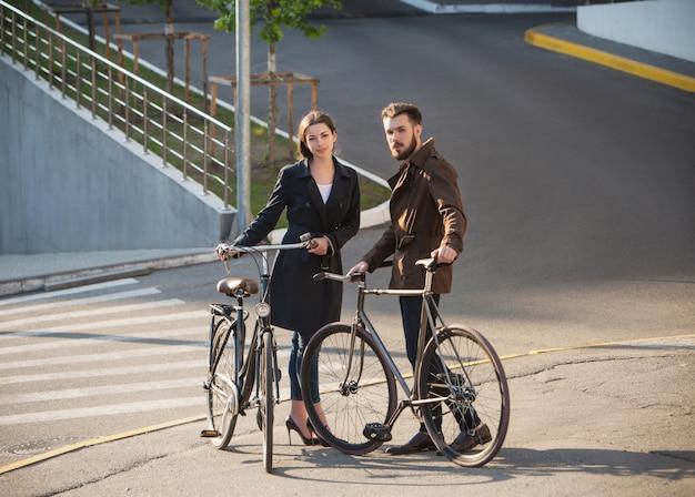 Pareja joven con una bicicleta frente a la ciudad