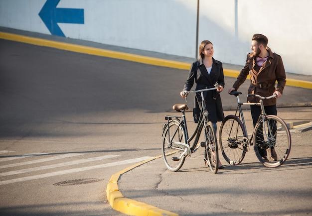 Pareja joven en bicicleta frente a la ciudad