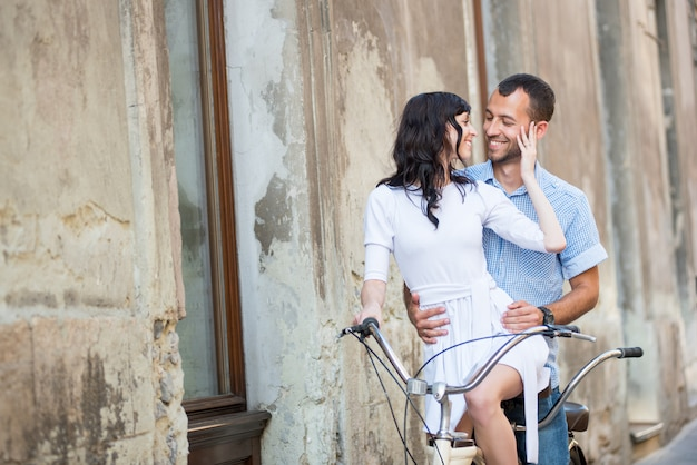 Pareja joven en bicicleta tándem retro en la calle de la ciudad