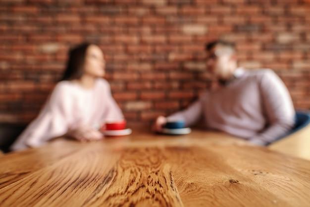 Pareja joven borrosa sentado en la cafetería y tomando café