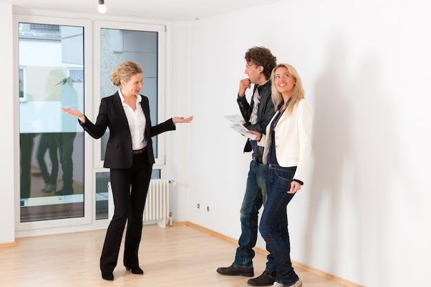 Pareja joven en busca de bienes raíces con agente inmobiliario femenino