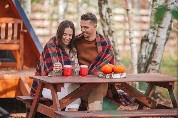 Pareja joven con café en el patio de su casa en otoño