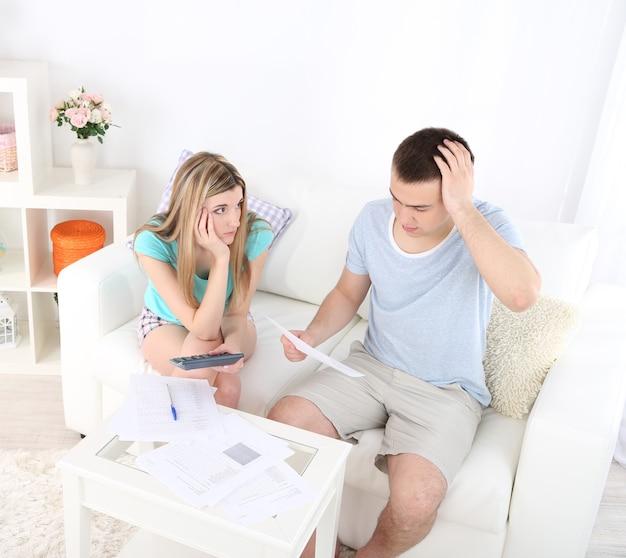 Pareja joven calculando las finanzas en el escritorio, en el fondo interior de una casa