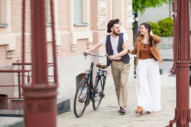 Pareja joven caminando con bicicleta y abrazos