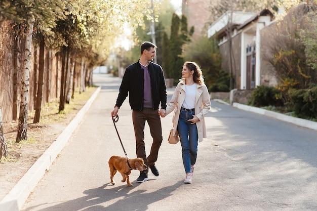 Pareja joven caminando por las escaleras con sus perros en una calle de la ciudad