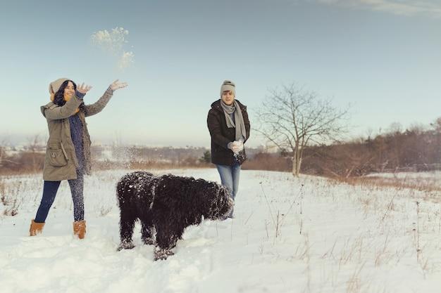 Pareja joven caminando con un perro en un día de invierno