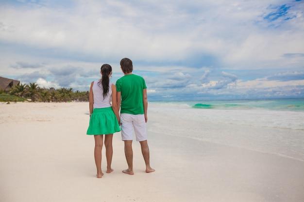 Pareja joven caminando por la playa exótica en un día soleado