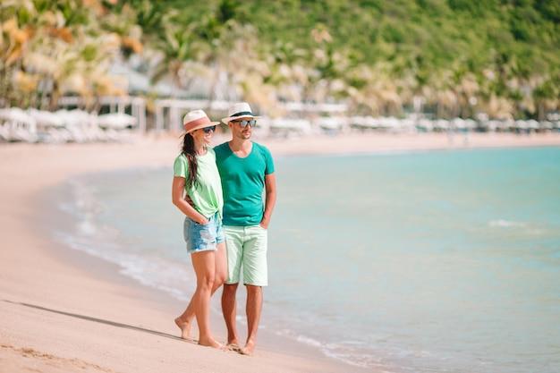 Pareja joven caminando en una playa tropical con arena blanca y agua turquesa del océano en la isla de antigua en el caribe