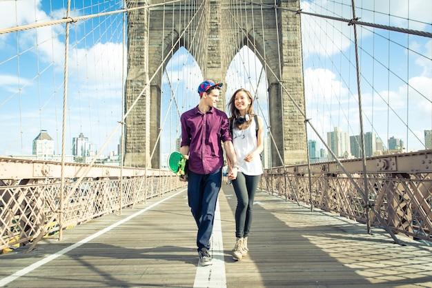 Pareja joven caminando por el puente de brooklyn