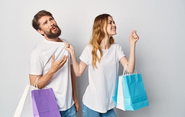 Pareja joven en camisetas blancas con paquetes en sus manos alegría de compras