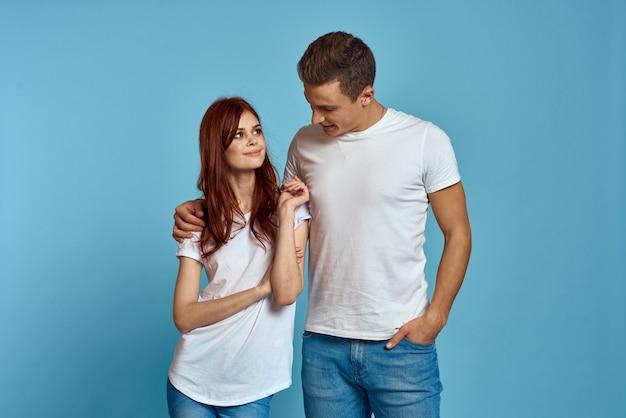 Pareja joven en camisetas blancas posando contra la pared azul