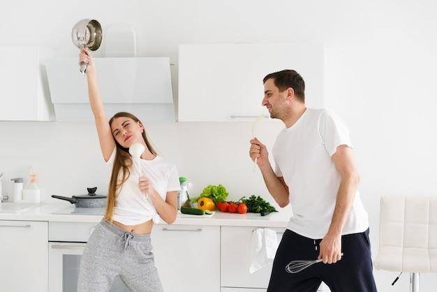 Pareja joven cantando mientras cocina