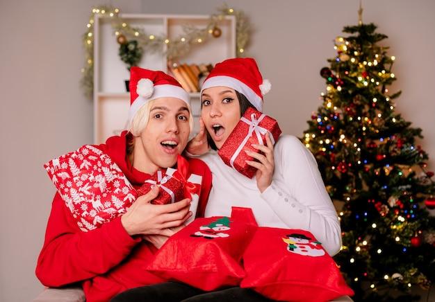 Pareja joven en casa en navidad con gorro de papá noel sentado en un sillón sosteniendo sacos y paquetes de regalo de navidad impresionó a chico y chica sorprendida, ambos mirando a cámara en la sala de estar