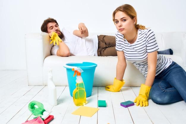 Una pareja joven cerca del sofá suministros de limpieza guantes protectores
