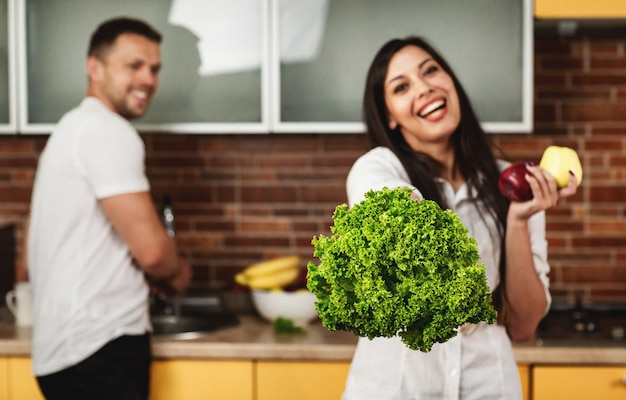 Pareja joven cocinando en la cocina. mujer sonriendo, sosteniendo lechuga y manzanas. el hombre del fondo. alimentación saludable.