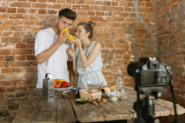 Pareja joven cocinando y grabando video en vivo para vlog y redes sociales