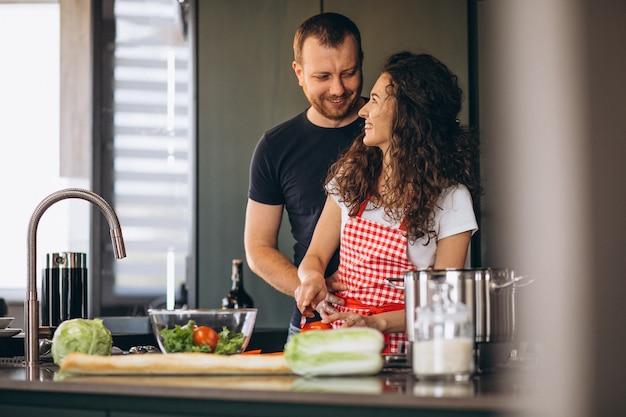 Pareja joven cocinando juntos en la cocina