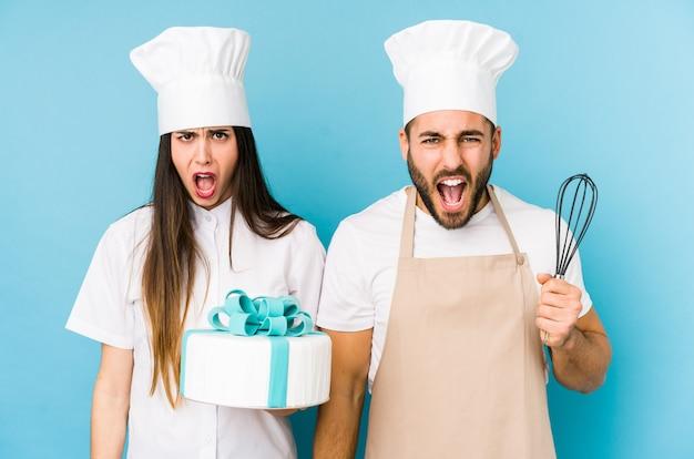 Pareja joven cocinando un pastel juntos gritando muy enojado y agresivo.