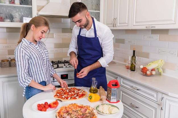 Pareja joven cocinando pizza con verduras y champiñones