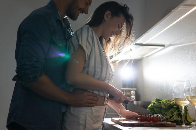 Pareja joven cocinando una sabrosa cena juntos en una cocina por la noche