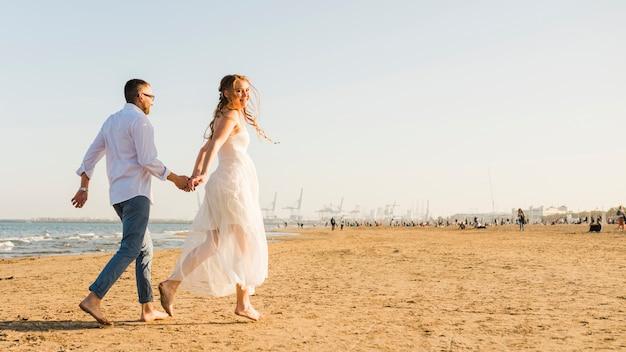 Pareja joven cogidos de la mano de otros corriendo en la playa de arena