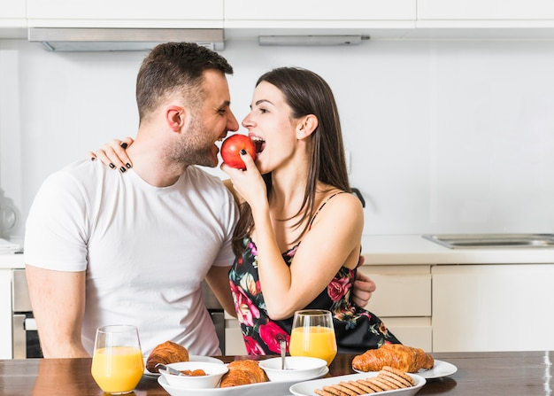 Pareja joven comiendo manzana con desayuno en mesa de madera