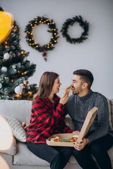 Pareja joven comiendo pizza en casa en navidad