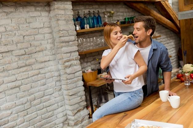 Pareja joven comiendo pizza y usando tableta digital junto a la mesa en el apartamento rústico