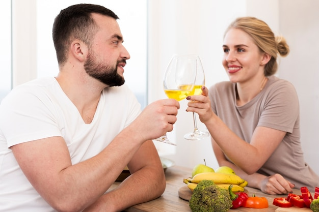 Pareja joven comiendo verduras y bebiendo juntos