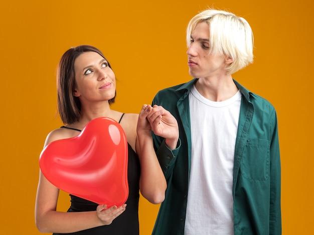 Pareja joven complacida mujer y hombre confiado en el día de san valentín tomados de la mano mujer sosteniendo globo en forma de corazón mirando hacia arriba hombre mirándola aislado en la pared naranja